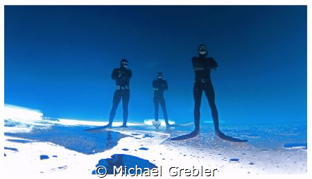 Three free-divers strike a pose upside down under the ice... by Michael Grebler