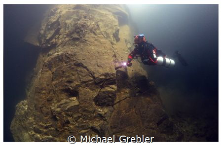 A side-mount diver descends along one of the supporting r... by Michael Grebler