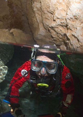 Freshwater cave, South Australia. Diver surfacing into ai... by Richard Harris