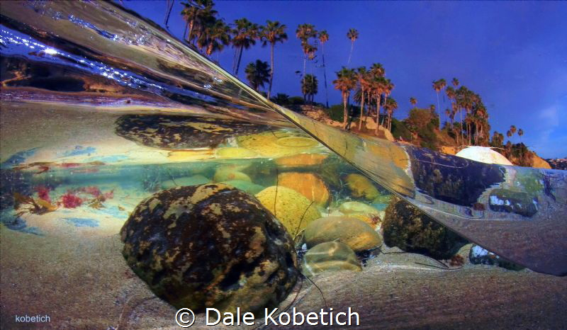 laguna beach half above and below...afternoon glow by Dale Kobetich