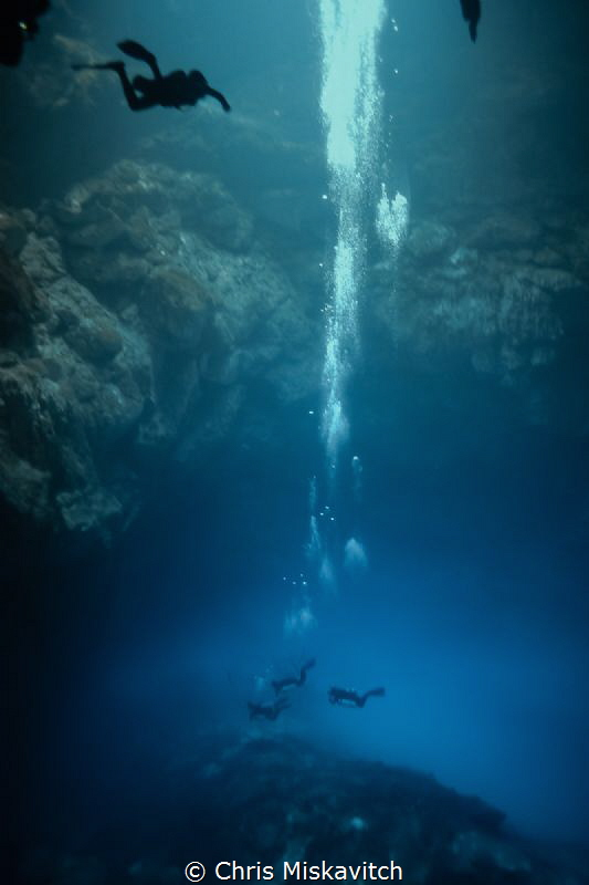"""""""The Pit"""" Cenote in Mexico, Divers enter the Halocline be... by Chris Miskavitch"""