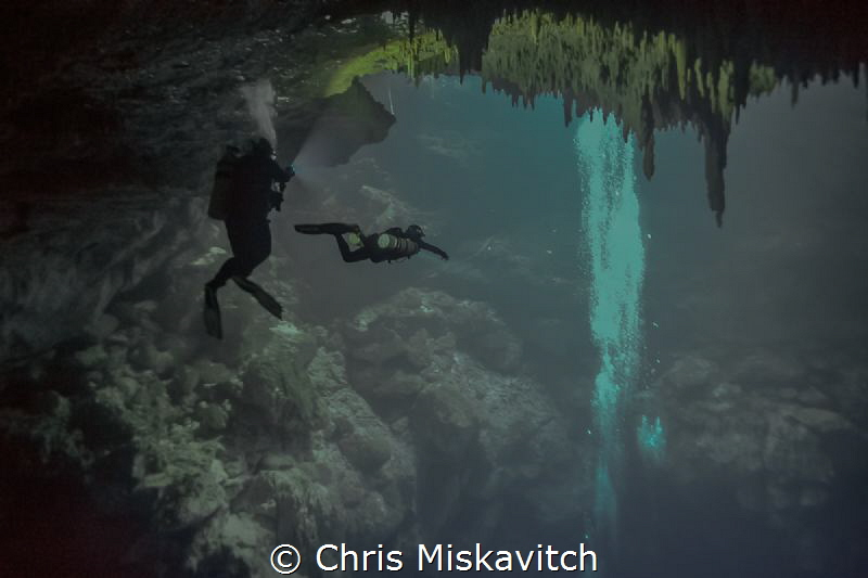 "Divers in the cenote ""The Pit"" Mexico by Chris Miskavitch"