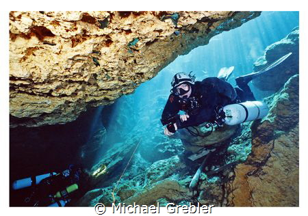 Side-mount diver entering the cavern section at Peacock S... by Michael Grebler