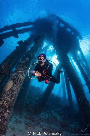Diver checking out the obscure concrete structures of the... by Nick Polanszky