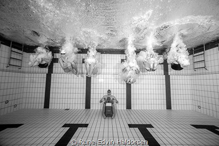 A group of lifesavers playing in the pool on a photo shoot. by Rune Edvin Haldorsen