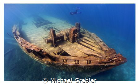 A skin diver swims down the port side of the wreck of the... by Michael Grebler