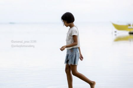 Girl by the shore with boat by Wayne Jones