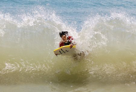 My son bodyboarding, gets hit by a wave returning from sh... by Helen Brierley