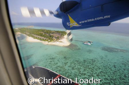 Seaplane coming in to land at the resort i work at. Landa... by Christian Loader