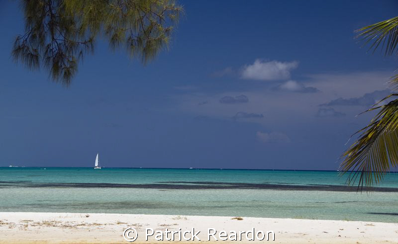 A sailboat passes by Cayman Kai, on the North shore of Gr... by Patrick Reardon