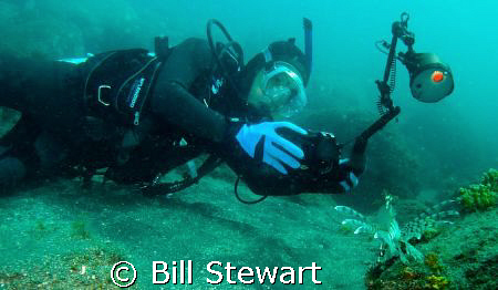My friend Junji photographing a lionfish during a dive at... by Bill Stewart