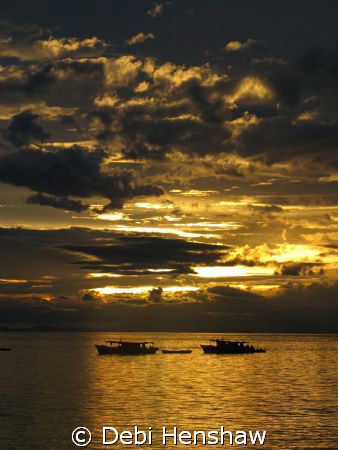 Sunset looking over dive boats moored off Mabul Island. S... by Debi Henshaw