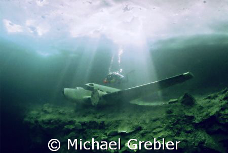 Diver with airplane under the ice at Morrison's Quarry. N... by Michael Grebler