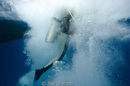 Bubbles surroundnig a diver after entering the water from... by Joe Graham