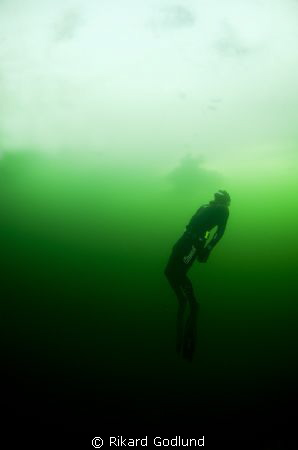 Freediver diving under the ice in Sweden by Rikard Godlund