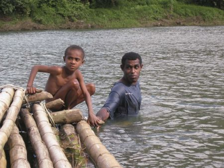 Fiji. A boy and his father pushing a bamboo raft. Shot wi... by Steven Pahel