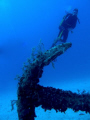 A diver hovers over a large anchor