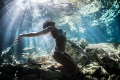Freediver Model Natalia embracing sunlight beaming through waters surface cenote Dos Ojos Mexico
