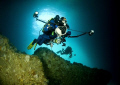 Photographers. Divers swimming sea cave Poor Knights Islands New Zealand. Photographers Zealand