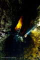 Cave diver descends down moulth fire looking clouds his head swirling tannic river water. water