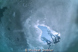 Looking up at free divers getting ready to dive from the ... by Michael Grebler