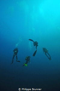 Divers in the blue for safety stop. by Philippe Brunner