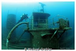 A diver checks her light before entering the wheelhouse o... by Michael Grebler