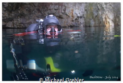 Cave diver at the surface of a flooded mine, near Bucking... by Michael Grebler