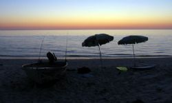 Remnants of a good day at the beach ... umbrellas, boat a... by Penny Murphy