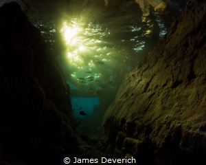 Sunset under the Jetty at Wakatobi. Golden rays came down... by James Deverich