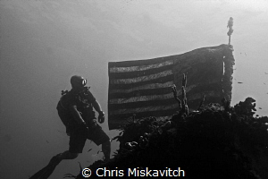 Diver and American flag on the wreck of the Spiegel Grove. by Chris Miskavitch