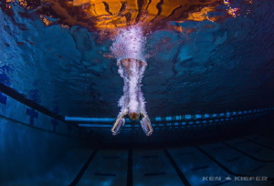 Diver from a high dive entering the water in a way to min... by Ken Kiefer