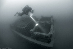 marine biologist diving on an artificial reef by Mathieu Foulquié