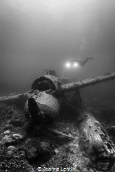 A diver exploring a WWII JAKE Sea Plane in Palau. by Joanna Lentini
