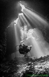 Cathedral lighting illuminates diver inside a cave at St ... by Gabriel De Leon Jr