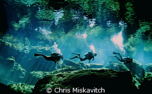 Divers heading back to the opening in Cenote.... by Chris Miskavitch