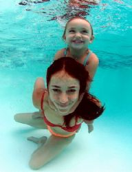 mother and child enjoy the warm pool water. relaxed. take... by Fiona Ayerst