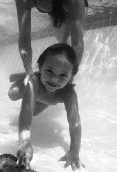 black and white image of child enjoying being underwater ... by Fiona Ayerst