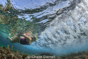 """""""Suspended""""  A Snorkeler prepares to duck under a small ... by Chase Darnell"""