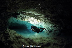 """A diver in a passage known as """"River Run"""", in the freshwa... by Lee Newman"""