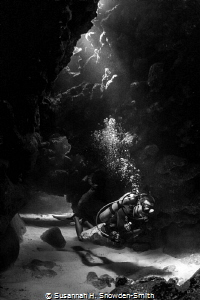 Light filters onto a diver as he emerges from a swim through by Susannah H. Snowden-Smith