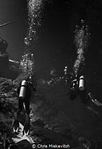 Divers exporing the Cenote by Chris Miskavitch