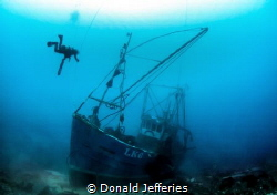 Silent Memory Diver exploring the wreck of a small fishi... by Donald Jefferies