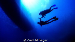Swimming under the boat on a nice, sunny day. by Zaid Al Sager