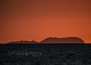 Sunset colours surrounding the amazing Apo Island as seen... by Jan Morton