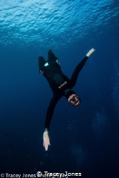 Free diver falling towards the camera with open arms by Tracey Jones