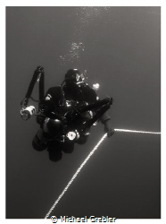 An underwater photographer in side-mount waits out his de... by Michael Grebler