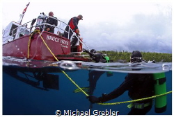 Divers board the dive boat shortly after the passing of a... by Michael Grebler