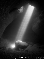 "The sunlight through the siphon of El Moraig"" cave in Pob... by Carlos Ortolà"