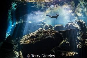 Freediver enjoys the tranquility of the crystal clear wat... by Terry Steeley